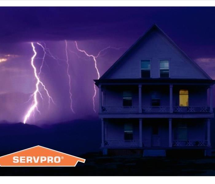 Lightning striking behind a house with SERVPRO logo